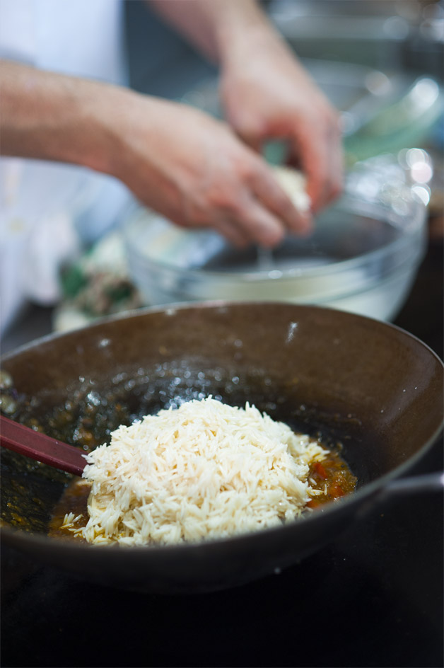 Adding rice to the stove's pot