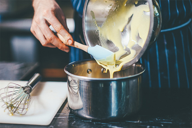 Custard mixture being poured into a heating pot