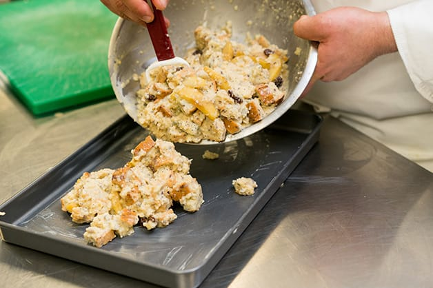 Pouring bread pudding into a baking dish