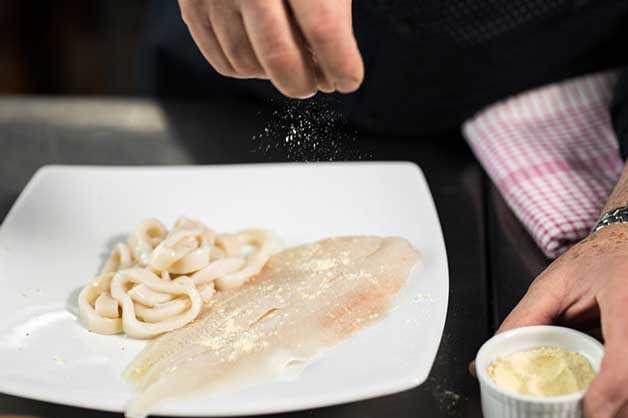 Image of the fish and calamari being seasoned