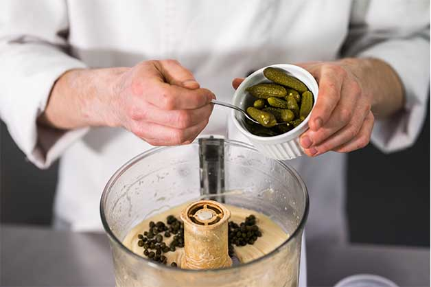 Chef adding pickles to the mayonnaise