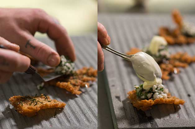 Chef adding the tartare on the cracker