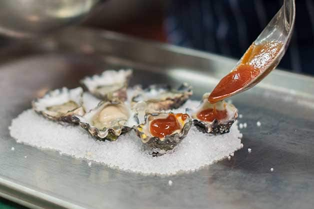 The chef adds a spoon of sauce to each oyster