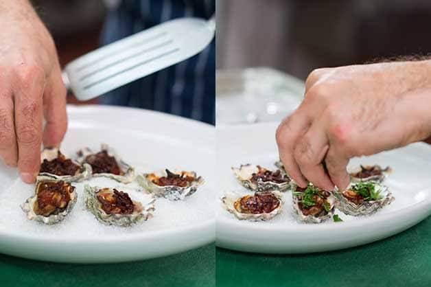 The chef finishes off the dish by adding parsley to each oyster
