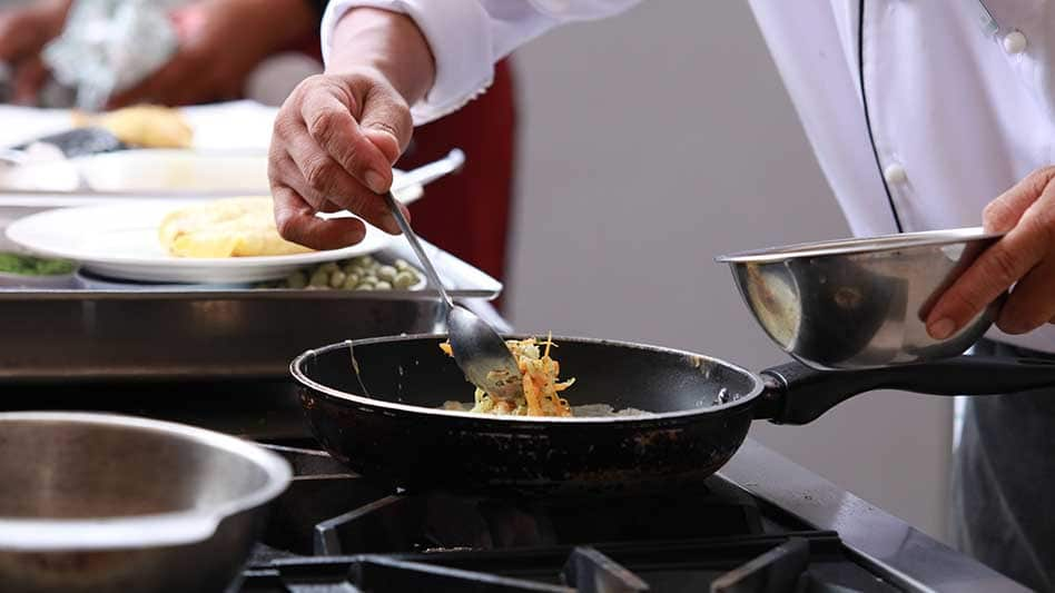 A chef is seen plating up a dish
