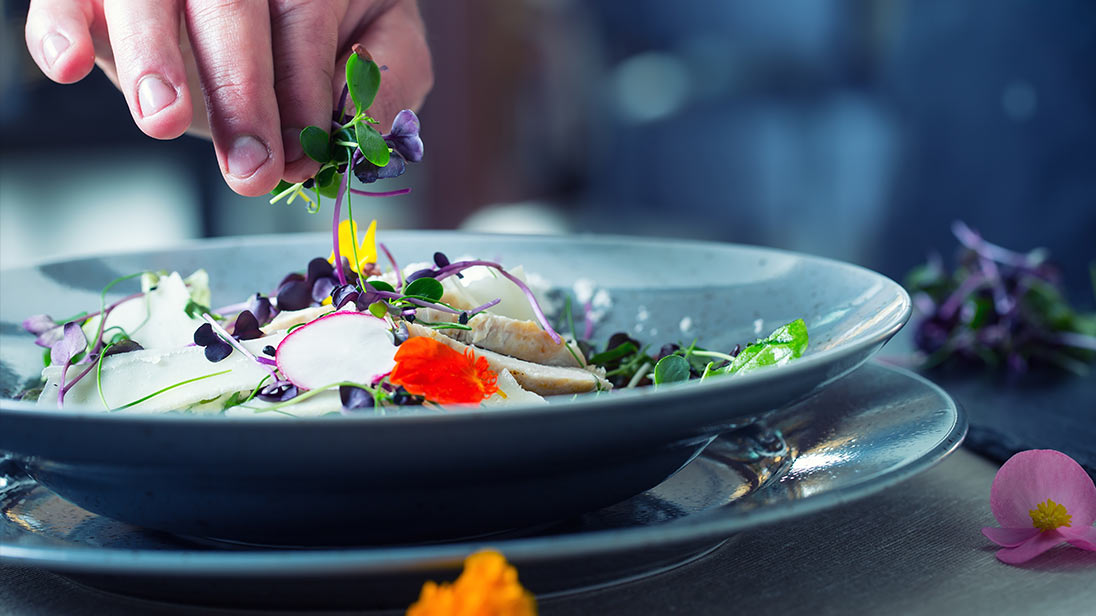 Image of a chef placing florals on a dish