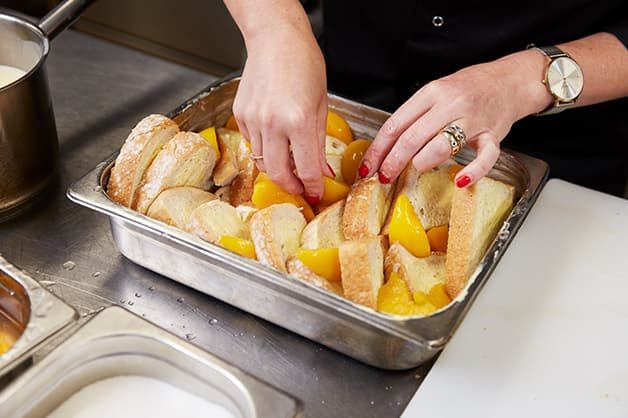 The chef is placing the peaches inbetween the slices of bread