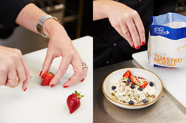 The chef is pictured slicing the strawberries and adding them and blueberries to the bircher