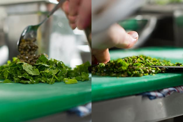 The chef is pictures slicing the fresh herbs and capers