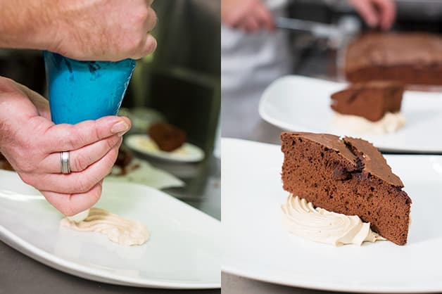 Here the chef is pipping the cream and placing cake on top