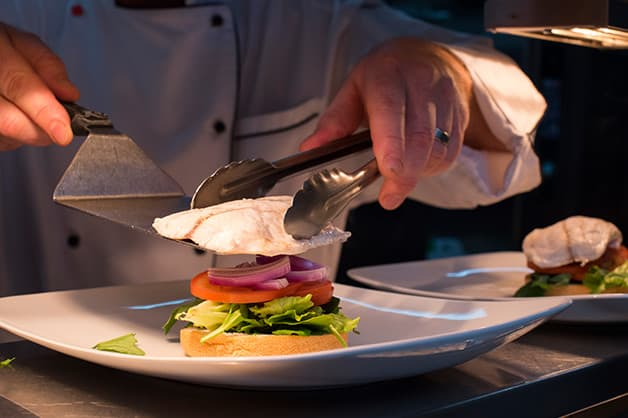 The chef is seen adding the barramundi to the burger