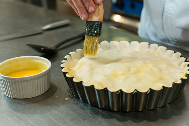 The chef brushes the lid of the pie with the egg wash