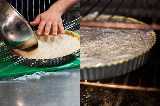The chef fills the pastry with rice for blind baking