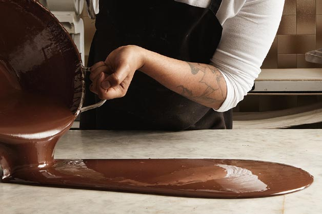 Image shows a chef tempering chocolate