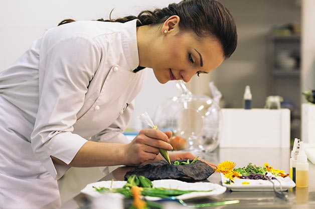 This picture shows a female chef plating a meal