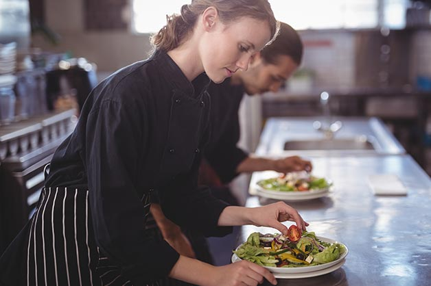 This shows two young female chefs working in the kitchen
