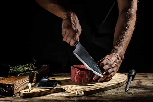 The image shows a chef using the knife
