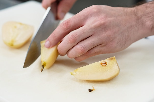 Slicing the poached pears once cooled