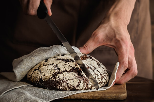 Image of a bread knife slicing through a loaf of bread