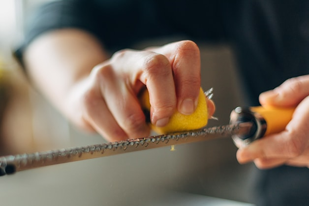 Chef is seen grating a lemon on a microplane