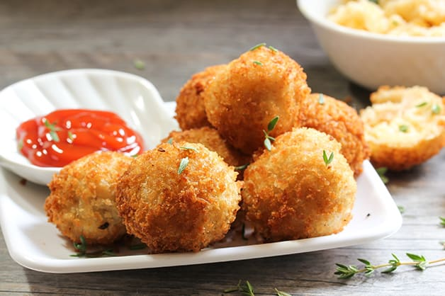 Image shows golden fried croquettes next to sauce