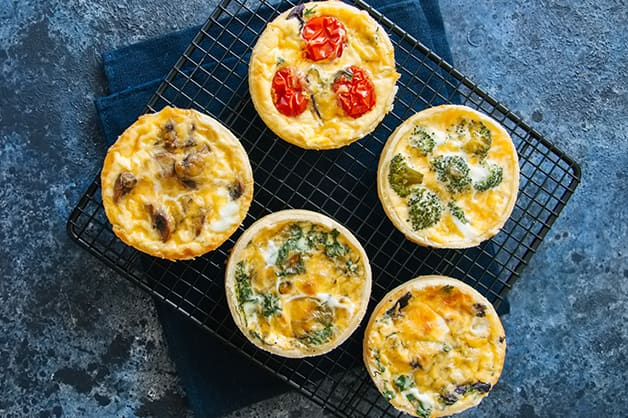 Five different tarts on a plate are pictured