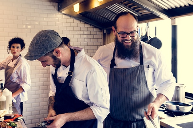 Image shows three chefs working in the kitchen