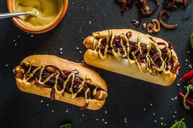 Photo of two hot dogs with onion