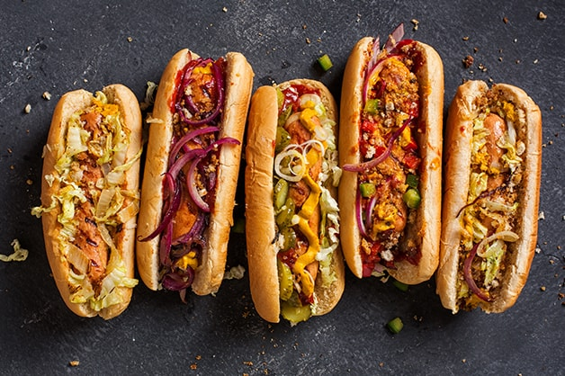 Image of five hot dogs with toppings