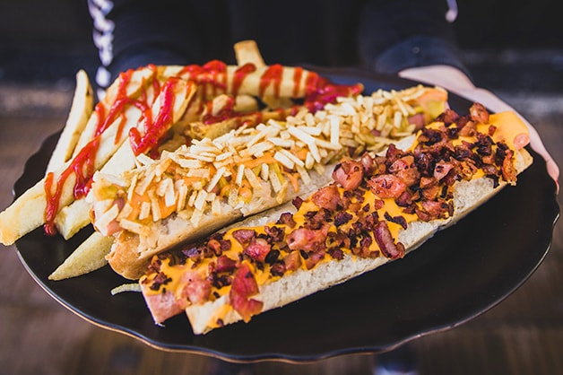 Photo of hot dog with over the top toppings