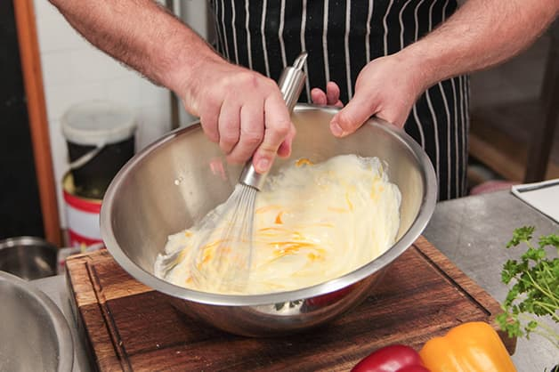 Chef is seen Combining White Wings Batter Mix and Eggs