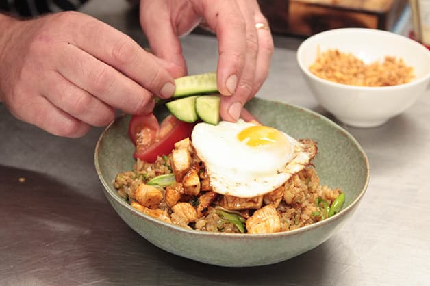 Image of the chef adding a fried egg to the dish