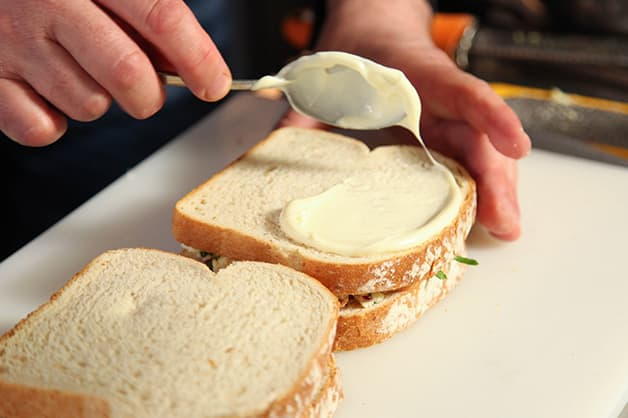 Chef spreads the Praise Mayonnaise on the bread
