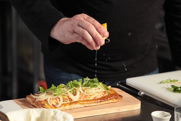Image of the chef squeezing lemon juice over the tart