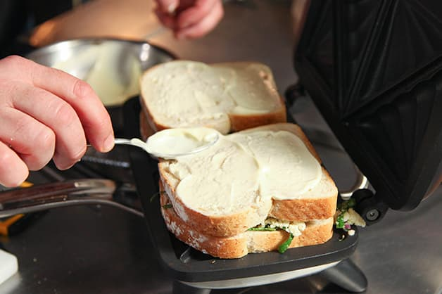 Chef puts the sandwich in the jaffle machine