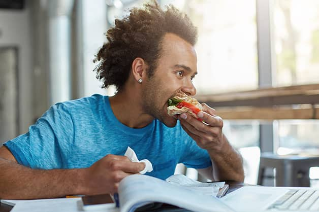 Man eating at a cafe while working