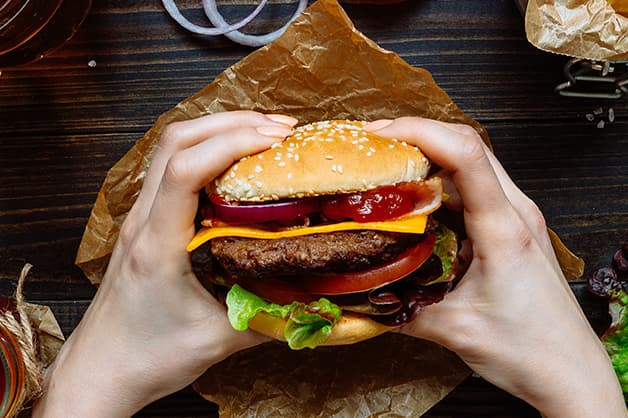 Image of a person holding a burger with both hands