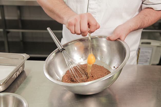 Adding an egg to the brownie mix