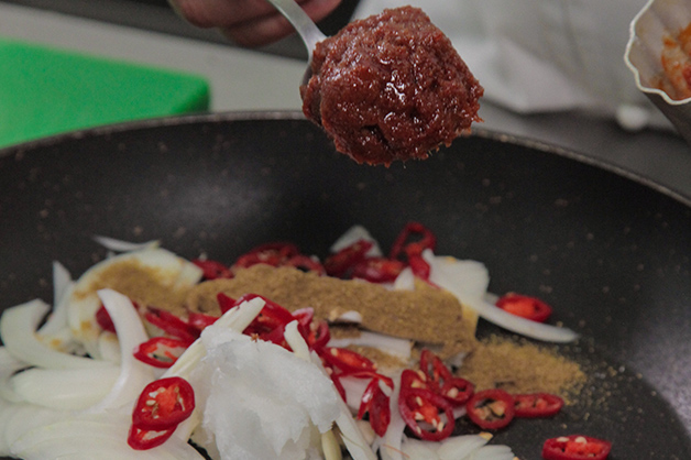 Adding chilli and paste to a pan